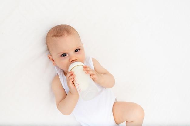 Babyjongen liggend op het bed in de kinderkamer op zijn rug en met een fles melk, de baby voeden, babyvoeding concept