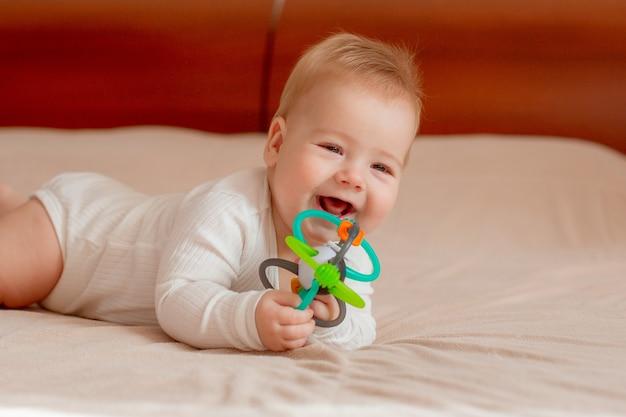 Babyjongen ligt op zijn buik met een stuk speelgoed op het bed in de slaapkamer