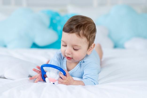 Babyjongen met een knaagdier voor tandjes krijgen of een rammelaar op het bed om te slapen