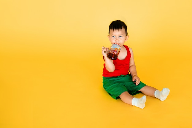 Babyjongen met fles of kruik sap of water in pop-artstijl met gele muur