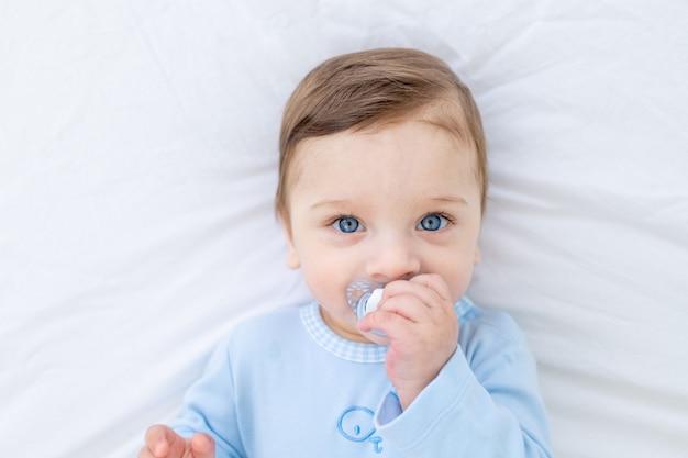 Babyjongen met fopspeen op bed alvorens naar bed te gaan in blauwe romper, gelukkige gezonde kleine baby