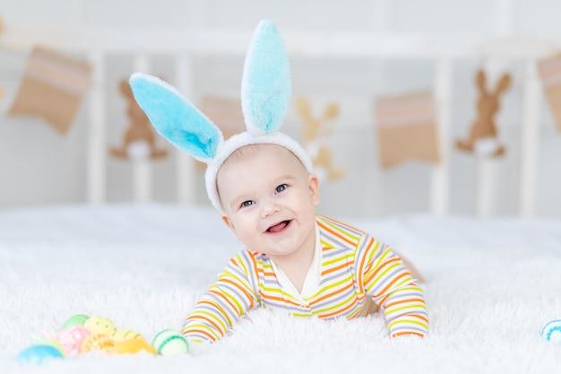 Babyjongen met konijnenoren op zijn hoofd liggend op het bed met paaseieren, leuke grappige glimlachende kleine baby.