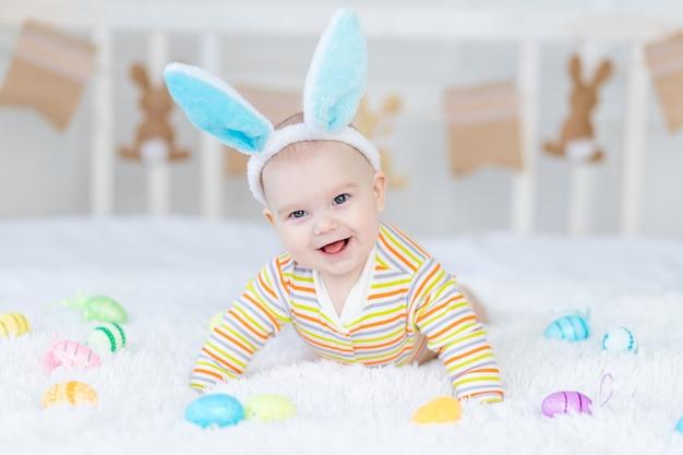 Babyjongen met konijnenoren op zijn hoofd liggend op het bed met paaseieren, schattige grappige lachende kleine baby. het concept van pasen.