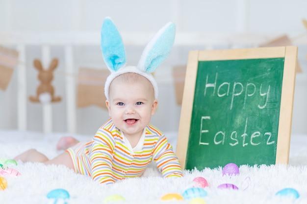 Babyjongen met konijnenoren op zijn hoofd ligt met de inscriptie happy easter op het bed met paaseieren, schattige grappige lachende kleine baby. het concept van pasen.