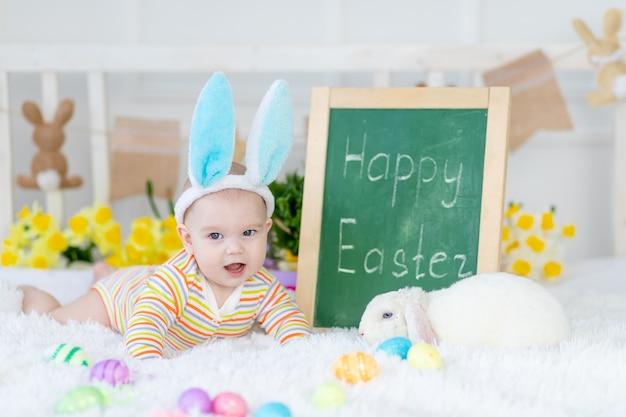 Babyjongen met konijnenoren op zijn hoofd ligt met de inscriptie vrolijk pasen op het bed met paaseieren, leuke grappige glimlachende kleine baby.