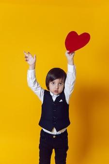 Babyjongen met rood papier hart in kostuum staat in gele muur op valentijnsdag