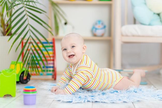 Babyjongen onder het speelgoed in de kinderkamer, schattige grappige lachende kleine baby die op de vloer speelt, het concept van de ontwikkeling van kinderen en spelletjes