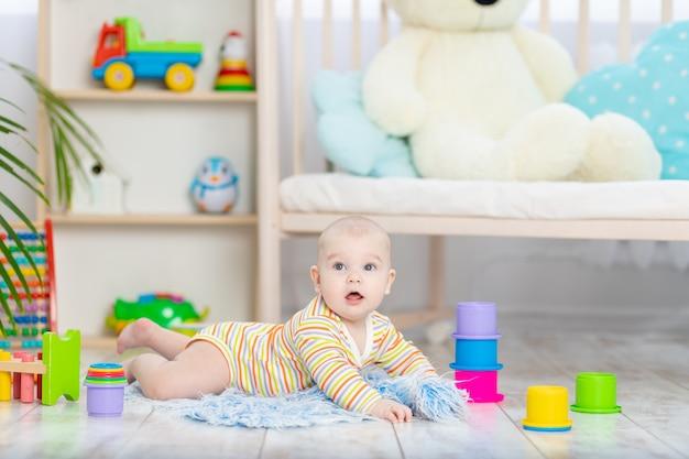 Babyjongen onder het speelgoed in de kinderkamer, schattige grappige lachende kleine baby spelen op de vloer, het concept van de ontwikkeling van kinderen en spelletjes