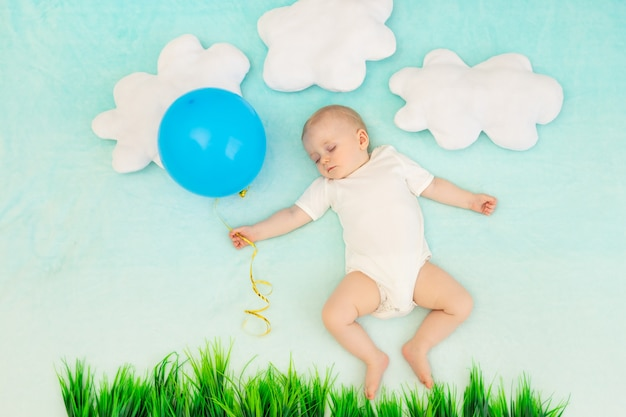 Babyjongen op een blauwe achtergrond tussen de wolken met een ballon die slaapt
