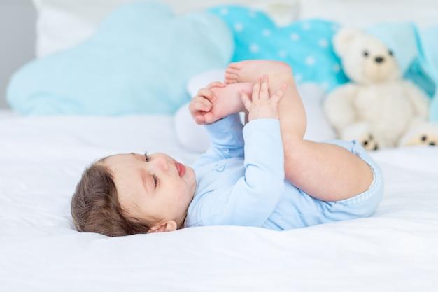 Babyjongen op het bed in een blauwe romper spelen met zijn voeten, gelukkige gezonde kleine baby