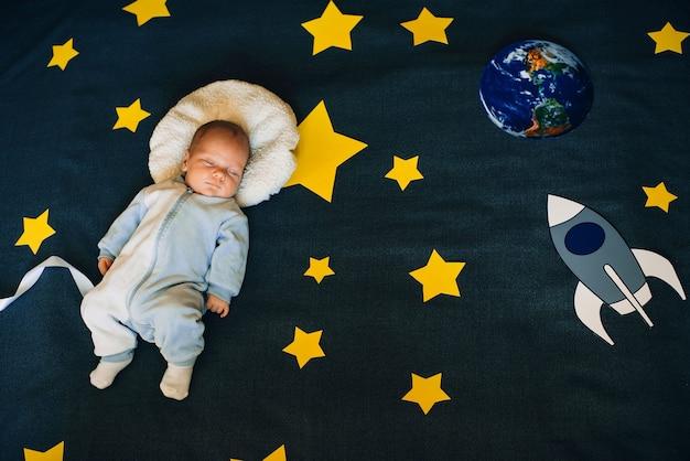 Babyjongen slaapt en droomt van zichzelf als astronaut in de ruimte