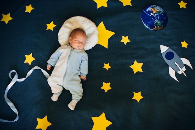Babyjongen slaapt en droomt zichzelf als een astronaut in de ruimte