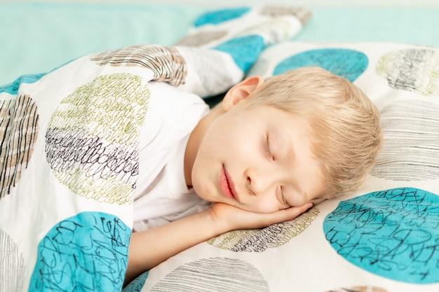 Babyjongen slaapt in zijn bed thuis.