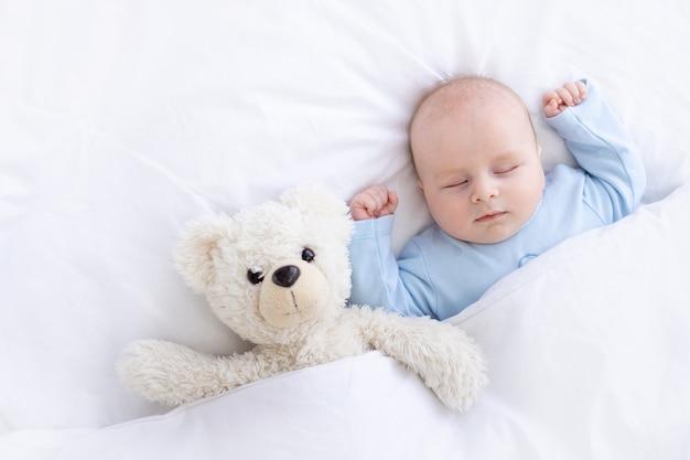 Babyjongen slaapt op het bed, liggend op zijn rug met een knuffelbeer in blauwe pyjama