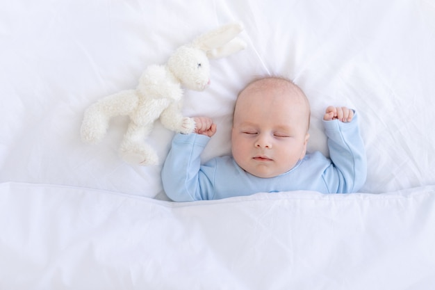 Babyjongen slapen op het bed liggend op zijn rug met een knuffel hazen in blauwe pyjama