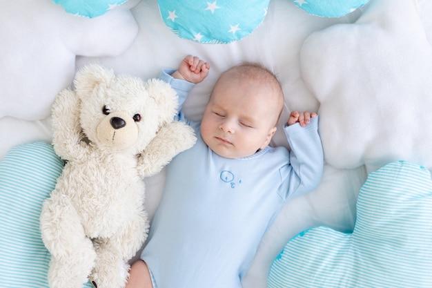 Babyjongen slapen op het bed liggend op zijn rug met een zachte teddybeer tussen de kussens