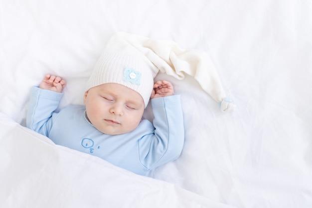 Babyjongen slapen op het bed liggend op zijn rug onder de deken