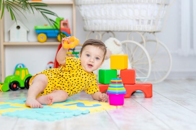 Babyjongen speelt in de kinderkamer in een gele bodysuit met felgekleurd speelgoed