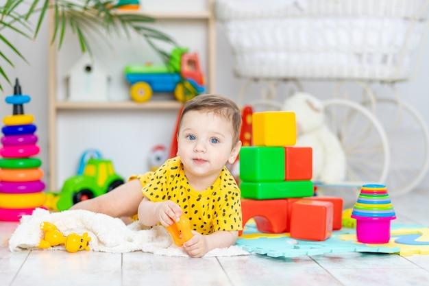 Babyjongen speelt in de kinderkamer in een gele bodysuit met helder kleurrijk speelgoed