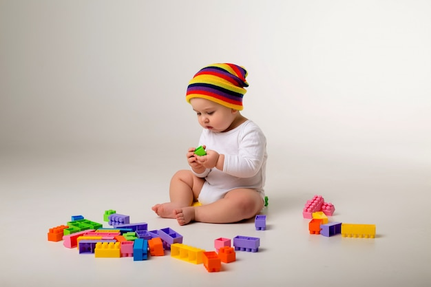 Babyjongen speelt met een veelkleurige aannemer op een witte muur