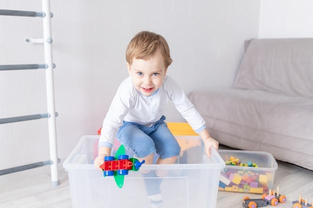 Babyjongen speelt thuis, klimt uit de doos