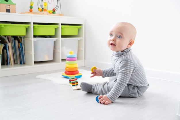 Babyjongen spelen in piramide en houten speelgoed. ontwikkeling van vroege kinderen.