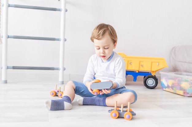 Babyjongen spelen met houten speelgoed thuis op de vloer