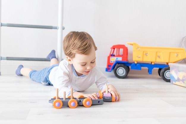 Babyjongen spelen met houten speelgoed thuis op de vloer.