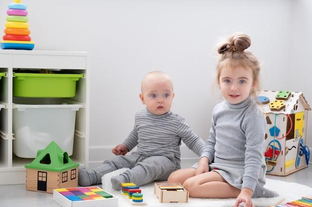 Babyjongen spelen met oudere zus met houten speelgoed. ontwikkeling van vroege kinderen.