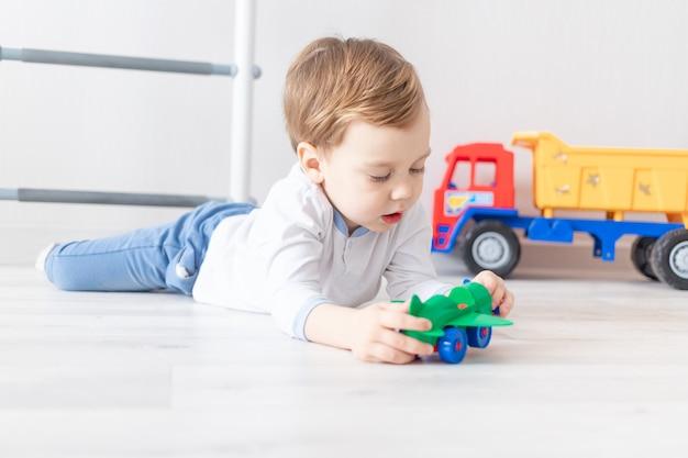 Babyjongen spelen op de vloer van het huis met een vliegtuig, het concept van een kinderspel.