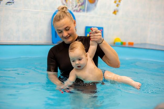 Babyjongen traint om in het zwembad te zwemmen met een trainer