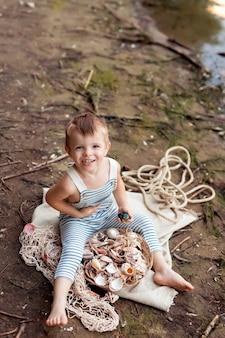 Babyjongen verkleed als zeeman op een zandstrand met schelpen aan zee