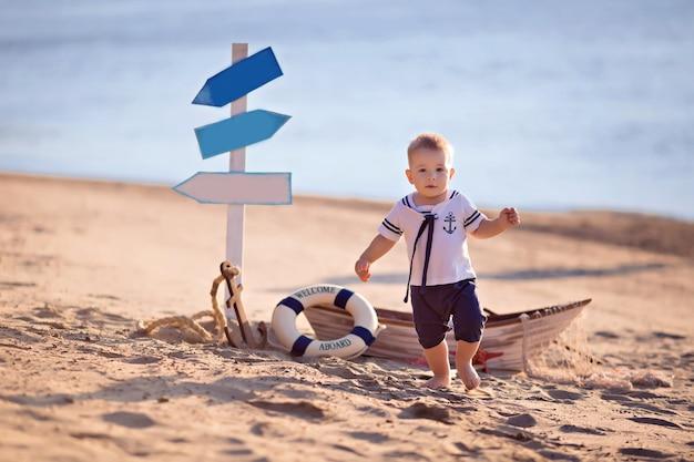 Babyjongen verkleed als zeeman op een zandstrand