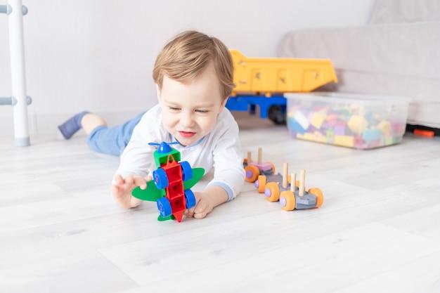 Babyjongen verzamelt de vliegtuigbouwer op de vloer van het huis het concept van het spel van het kind