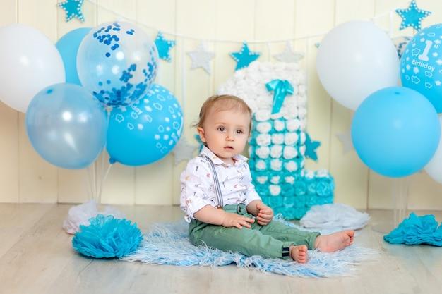 Babyjongen viert 1 jaar met cake en ballonnen, gelukkige jeugd, kinderverjaardag