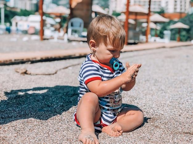 Babyjongen weinig op het strand speelt met zand. het concept van toerisme en vrije tijd.