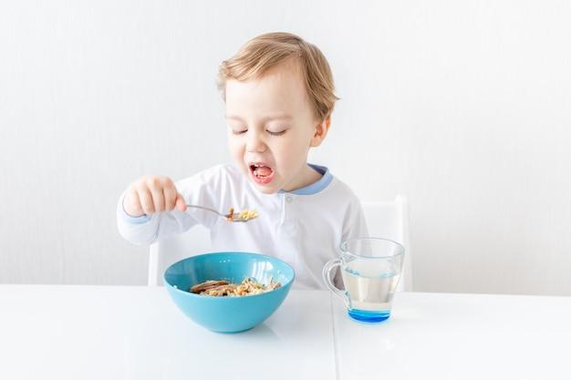 Babyjongen wil zichzelf niet eten met een lepel thuis, het concept van voedsel en voeding voor kinderen.