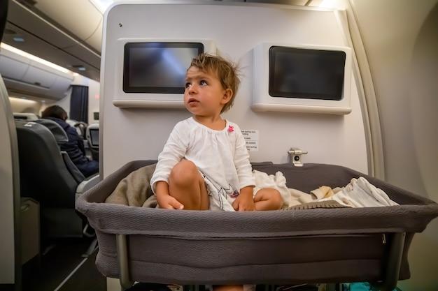 Babyjongen wordt wakker terwijl hij in de wieg op het vliegtuig slaapt. babypassagier aan boord. eerste vlucht