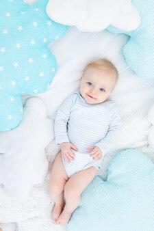 Babyjongen zes maanden oud liggend op een bed met zachte blauwe kussens, lachende blonde baby