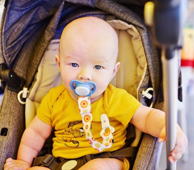 Babyjongen zit in de wandelwagen in de zomer