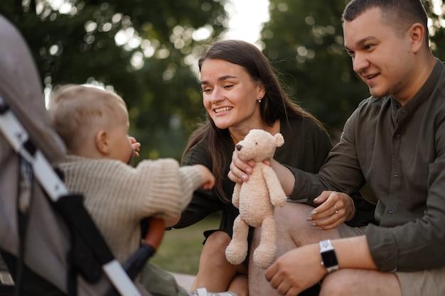 Babyjongen zit in een kinderwagen zijn jonge ouders op de achtergrond zittend op stenen balustrade looki