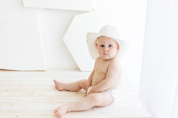 Babyjongen zit in luiers in een witte hoed