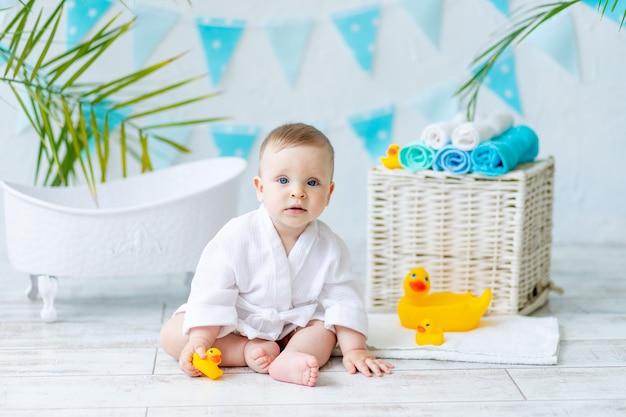 Babyjongen zit na het baden in het bad in een wit gewaad met een rubberen eend en een handdoek, het concept van hygiëne en wassen.