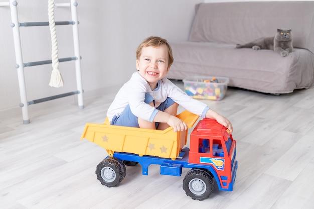 Babyjongen zitten of rijden in een typemachine thuis, het concept van het spel van een kind