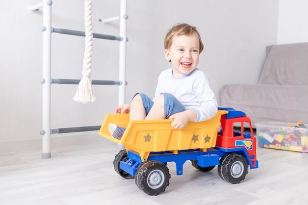 Babyjongen zitten of rijden in een typemachine thuis het concept van het spel van een kind