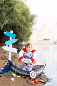 Babyjongen zittend in een boot, verkleed als zeeman op een zandstrand met schelpen aan zee