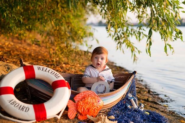 Babyjongen zittend in een boot, verkleed als zeeman, op een zandstrand met schelpen aan zee