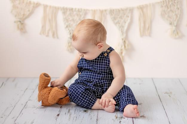 Babyjongen zittend met een teddybeer speelgoed op de vloer