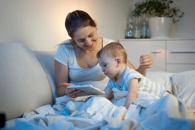 Babyjongen zittend op bed met moeder en 's nachts digitale tablet gebruiken