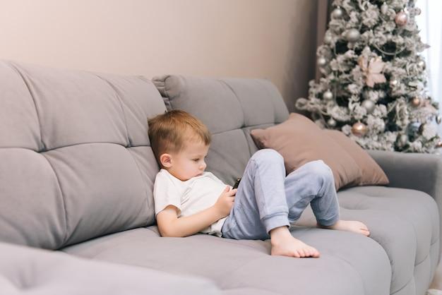 Babyjongen zittend op de bank met een telefoon in zijn handen, afhankelijkheid van kinderen van gadgets